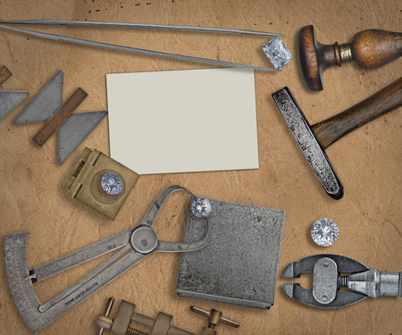 jeweler: vintage jeweler tools and diamonds over  working bench, blank business card for your text Stock Photo