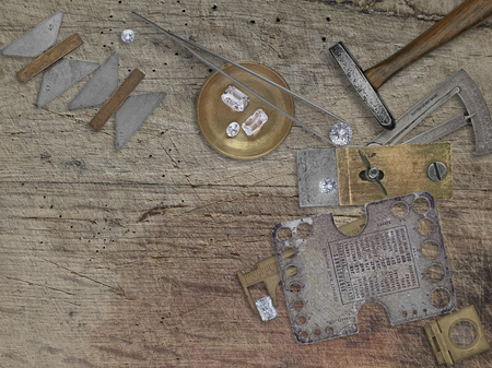 work table: vintage jeweler tools and diamonds over wooden bench, space for your business name