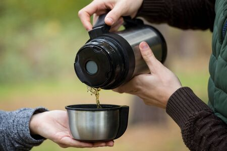 pours: Man pours tea from the thermos his girlfriend. Young couple at picnic in the autumn forest. Stock Photo