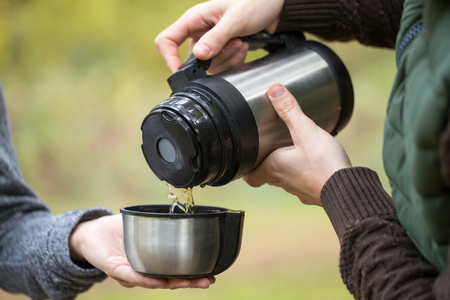 forest tea: Man pours tea from the hot container his girlfriend. Young couple at picnic in the autumn forest.