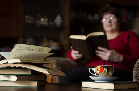 novel: Books and a cup of tea on the table. Woman reading novel. Lifestyle in retirement age. Stock Photo