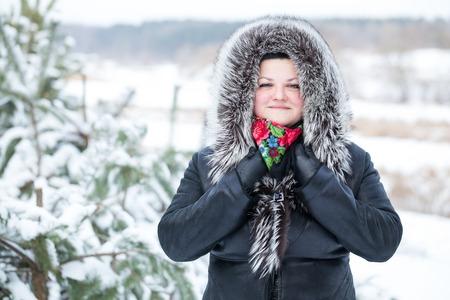 mujer alegre: La mujer se coloca cerca de los pinos j�venes. La mujer se pasea al aire libre en invierno. Bosque cubierto de nieve fresca despu�s de la tormenta de nieve. Foto de archivo