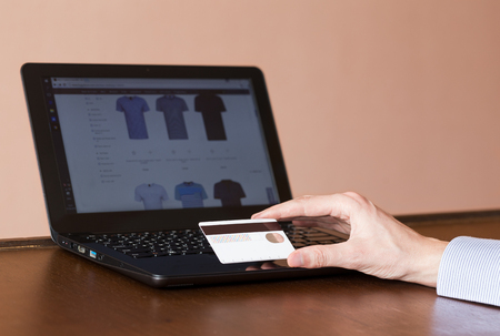 uses: Young man uses a bank card for online shopping. Stock Photo