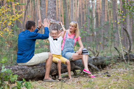 upbringing: Young family relaxing on the nature. Parents spend time with his son in the fun atmosphere.