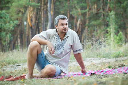 bedspread: Picnic in the forest. Man sits on the bedspread. Stock Photo