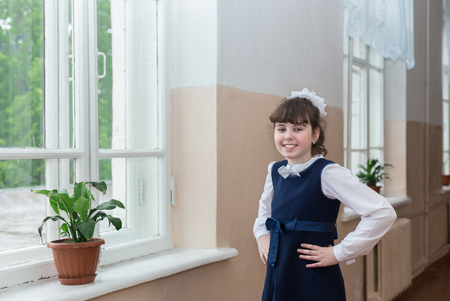 first day: The last day of school. Schoolgirl is standing in the school corridor near the window with a flower. Stock Photo