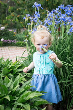 Little girl is standing in the flower garden.