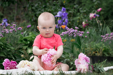Little girl is playing with flowers in the park.