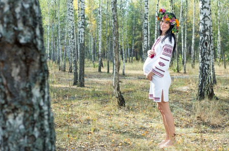 Pregnant girl is standing in a birch grove with a wreath on her head.