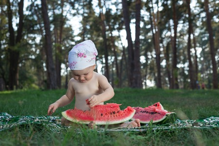bedspread: Baby with watermelon in the park.
