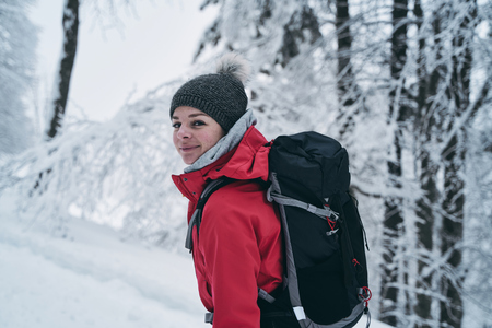 portrait of a happy young caucasian woman spending her free time hiking outdoors in nature, covered with snow. Stock fotó