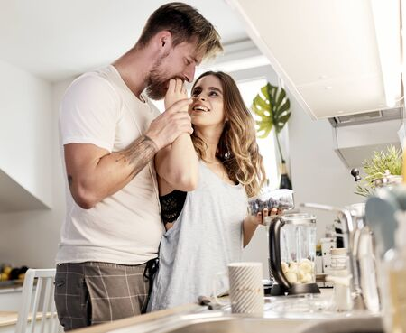 cute caucasian couple spending their morning in the kitchen, prepairing coffee