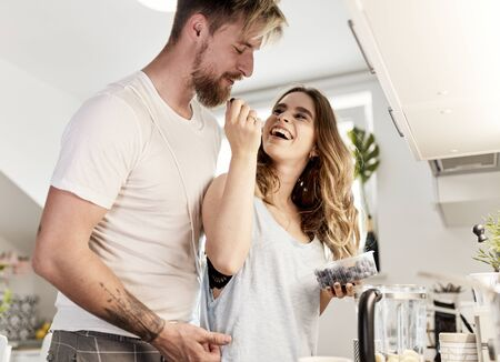 cute caucasian couple eating blueberries in the kitchen