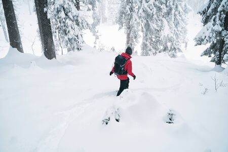 young caucasian woman spending her free time hiking outdoors in nature, covered with snow.