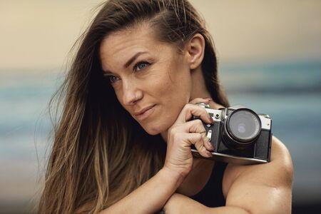 portrait of a beautiful brunette photographer holding a vintage camera. Stok Fotoğraf
