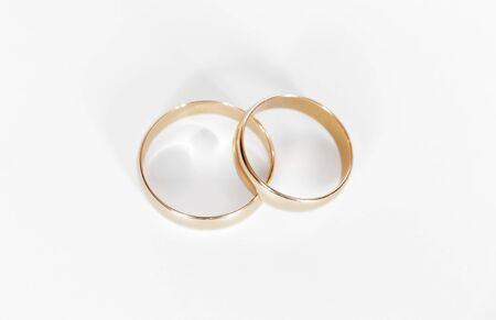 Two gold wedding rings close up on a white background Stock Photo