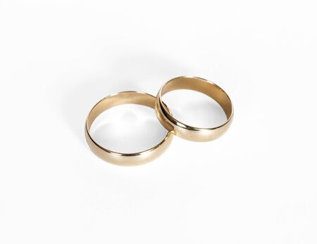 vows: Two gold wedding rings close up on a white background Stock Photo