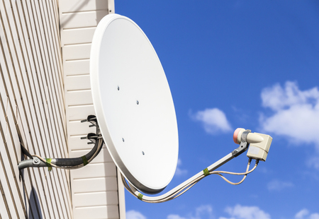 sattelite: Satellite dish mounted on the wall of a private house
