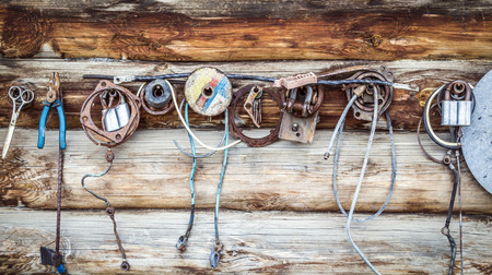 needless: Other small items hanging on the wooden wall of a rural buildings