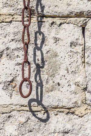 rusty chain: Old rusty chain hanging on a stone wall background