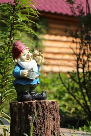 garden gnome: Little garden gnome figurine standing on a tree stump in the backyard Stock Photo