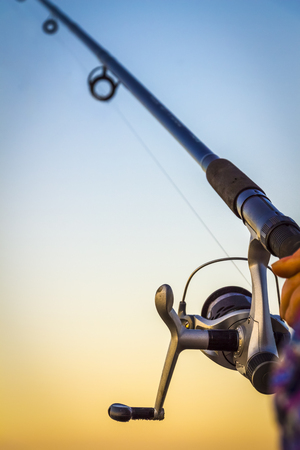 Fisherman fishing rod on the sunset close-up Stock Photo