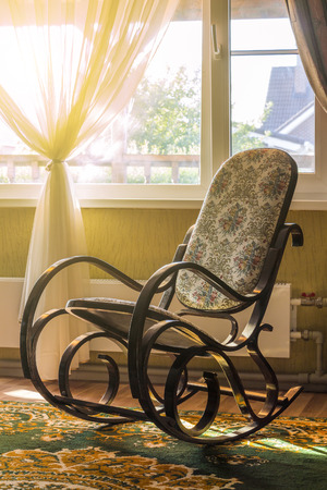 living room window: The rocking chair in the living room beside the window Stock Photo