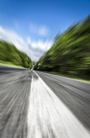De witte lijn op de weg, die in de verte afneemt, gaat omhoog bij hoge snelheid