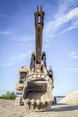 cargador frontal: Old yellow excavator on the background of blue sky Foto de archivo