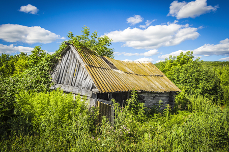 Old abandoned wooden hut, overgrown grass on a bright sunny summer day Stock Photo