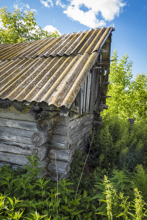 Part of the abandoned old wooden hut, overgrown with grass. Stock Photo