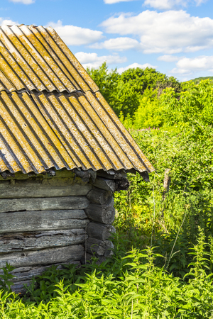 wooden hut: Part of the abandoned old wooden hut, overgrown with grass. Stock Photo
