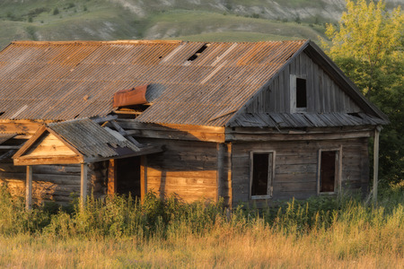 Old abandoned wooden house, overgrown grass on a bright sunny summer evening