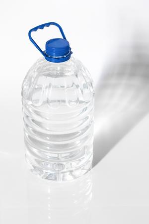 destilacion: Recipiente de plástico con agua en el fondo blanco primer plano.