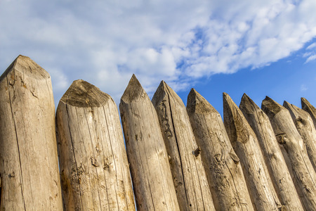 and the stakes: Protective fence of sharp wooden stakes closeup.