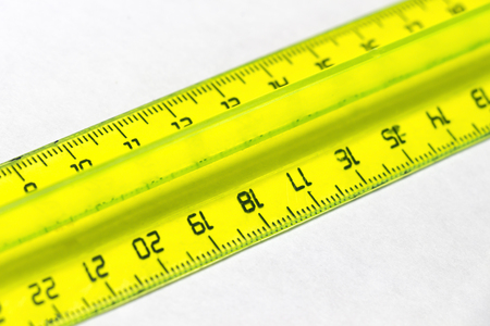 millimetre: Yellow plastic cleical ruler closeup on a white background. Stock Photo