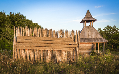 A wooden signboard on the fence and ancient Russian border checkpoint.