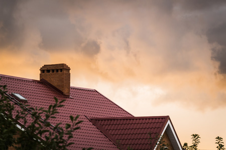 roof ridge: The red roof of the house on a background of strong clouds and setting sun.