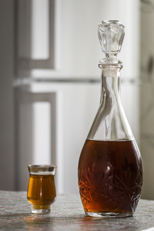 The Decanter Of Brandy And A Glass Are On The Kitchen Table Closeup. Stock  Photo
