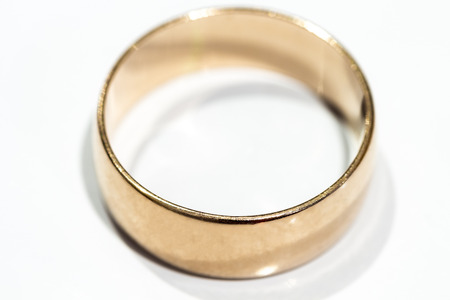 A wedding ring is a white table close up.