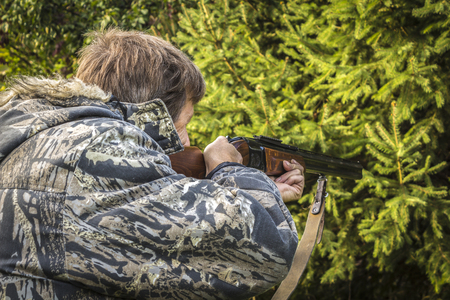 protective clothing: Hunter in protective clothing aiming a hunting rifle closeup.