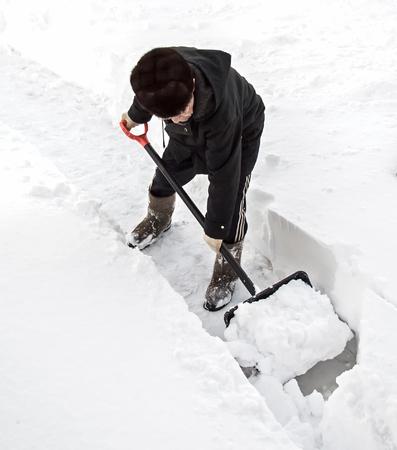 Een man verwijdert sneeuw van het spoor. Stockfoto