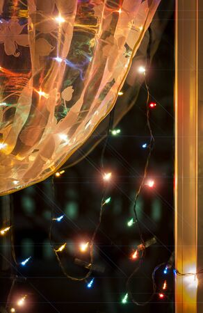 multy: Christmas lights in the window on the background of transparent tulle. Stock Photo