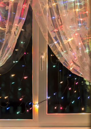 christmas lights in the window on the background of transparent tulle stock photo 68297327
