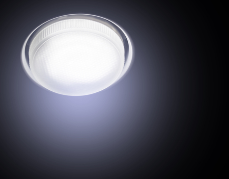 Ceiling Recessed LED lamp is lit close-up cold light on a black background. Stock Photo