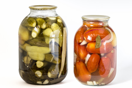 Bank of pickled cucumbers and a bank with salty tomato closeup on a white background.