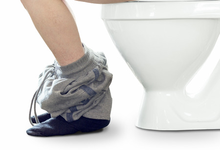whithe: The man is sitting on the toilet bowl close-up on a white background. Stock Photo