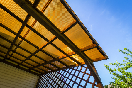 The roof of the veranda of orange polycarbonate on blue sky background. Stock Photo