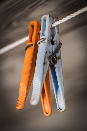 Plastic colored clothespins on a rope close-up.