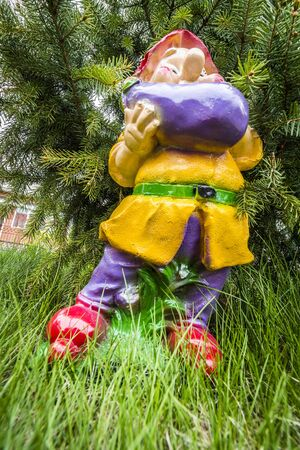 Little Garden Gnome Figurine Standing On A Tree Stump In The Backyard Stock  Photo